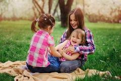 Τρεις μικρές αδελφές που έχουν πολύ παιχνίδι διασκέδασης μαζί υπαίθριο στο θερινό πάρκο στις διακοπές Στοκ Εικόνες