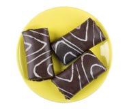 Τρεις μικροί ελβετικοί ρόλοι σοκολάτας στο κίτρινο πιατάκι στο λευκό Στοκ Φωτογραφία