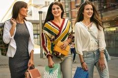 Τρεις μοντέρνες νέες γυναίκες strolling με τις τσάντες αγορών στοκ εικόνες
