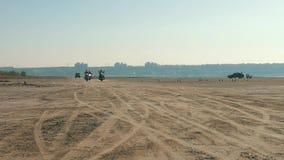 Τρεις μοτοσυκλετιστές που οδηγούν κοντά στην αμμώδη παραλία στην έρημο από μακριά Γύρος ποδηλατών φιλμ μικρού μήκους