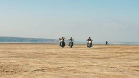 Τρεις μοτοσυκλετιστές που οδηγούν κοντά στην αμμώδη παραλία στην έρημο από μακριά Ελεύθερος γύρος απόθεμα βίντεο