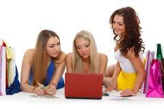 Τρεις νέες γυναίκες με το lap-top. Αγορές. Στοκ φωτογραφία με δικαίωμα ελεύθερης χρήσης