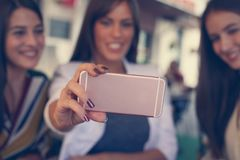 Τρεις νέες γυναίκες που κάνουν selfie στο έξυπνο τηλέφωνο Εστίαση στο τηλέφωνο Στοκ εικόνες με δικαίωμα ελεύθερης χρήσης