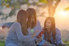 Τρεις νέες γυναίκες που κοιτάζουν στο κινητό τηλέφωνο Κορίτσια εφήβων Swag Outd Στοκ Εικόνες