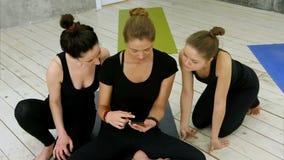 Τρεις νέες γυναίκες που μελετούν το asana γιόγκας χρησιμοποιώντας το smartphone μετά από το workout στην κατηγορία γιόγκας φιλμ μικρού μήκους