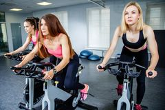 Τρεις νέες γυναίκες που στη γυμναστική, που ασκεί τα πόδια που κάνουν τα καρδιο ποδήλατα ανακύκλωσης workout στοκ φωτογραφία
