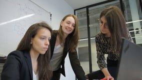 Τρεις νέες γυναίκες συζητούν το θέμα μπροστά από ένα lap-top στην αρχή απόθεμα βίντεο