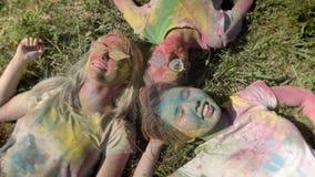 Τρεις νέες ευτυχείς πολυ-εθνικές φίλες βάζουν στη χλόη στο φεστιβάλ holi στην ημέρα το καλοκαίρι, έννοια φιλίας φιλμ μικρού μήκους