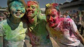 Τρεις νέες πολυ-εθνικές φίλες γελούν στο φεστιβάλ holi στην ημέρα το καλοκαίρι, έννοια φιλίας, χρώμα απόθεμα βίντεο