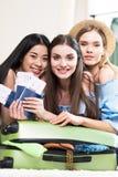 Τρεις νέες χαμογελώντας γυναίκες που κρατούν τα διαβατήρια και τα εισιτήρια συσκευάζοντας τη βαλίτσα Στοκ Εικόνες