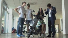 Τρεις νέοι επιλέγουν το μηχανικό δίκυκλο στην αίθουσα εκθέσεως αυτοκινήτων απόθεμα βίντεο