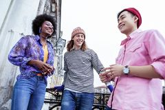 Τρεις νέοι μοντέρνοι σπουδαστές που αισθάνονται τον καλό χρόνο εξόδων από κοινού στοκ φωτογραφία με δικαίωμα ελεύθερης χρήσης