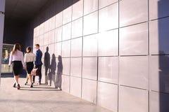 Τρεις νέοι, σπουδαστές, δύο κορίτσια και τύπος, πηγαίνουν πίσω ήρθαν Στοκ Φωτογραφίες