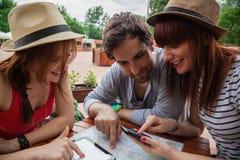 Τρεις νέοι τουρίστες στον καφέ Στοκ Εικόνες