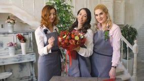 Τρεις νέοι όμορφοι ανθοκόμοι αρχιμαγείρων θέτουν το χαμόγελο κεκλεισμένων των θυρών με την έτοιμη ανθοδέσμη φρούτων απόθεμα βίντεο