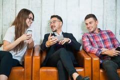Τρεις νέων λαβής smartphones κοινωνικός καθαρός συνομιλίας sms Διαδικτύου σε απευθείας σύνδεση Στοκ εικόνα με δικαίωμα ελεύθερης χρήσης