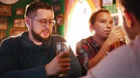Τρεις νεαροί άνδρες που πίνουν την μπύρα σε ένα μπαρ φιλμ μικρού μήκους
