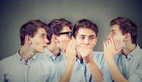 Τρεις νεαροί άνδρες που ψιθυρίζουν ο ένας τον άλλον και στο συγκλονισμένο έκπληκτο τύπο στο αυτί στοκ εικόνα