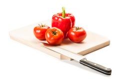 Τρεις ντομάτες, ένα κόκκινο πιπέρι, μαχαίρι και ξύλινος πίνακας Στοκ εικόνες με δικαίωμα ελεύθερης χρήσης