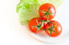 Τρεις ντομάτες κερασιών με τους μίσχους, τα πράσινα φύλλα μαρουλιού και ένα άσπρο πιάτο, που απομονώνονται στην άσπρη tabletop επ Στοκ Εικόνες
