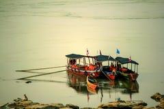 Τρεις ξύλινες βάρκες που επιπλέουν στο riverbank στοκ φωτογραφίες