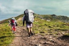 Τρεις οδοιπόροι που περπατούν στα βουνά Στοκ Φωτογραφίες