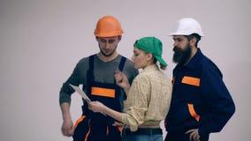 Τρεις οικοδόμοι συζητούν ένα νέο πρόγραμμα της οικοδόμησης ενός σπιτιού Έννοια της κατασκευής απόθεμα βίντεο