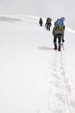 Τρεις ορειβάτες ανέρχονται τον παγετώνα στοκ εικόνα