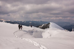 Τρεις οδοιπόροι που περπατούν κάτω από έναν απότομο βράχο λόφων βημάτων στο χωριό μετά από το μακρύ βουνό στο κρύο χειμερινού χιο Στοκ Εικόνα