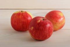Τρεις ολόκληρη ώριμη κόκκινη Apple που φωτογραφίζεται στην κινηματογράφηση σε πρώτο πλάνο Στοκ Εικόνες