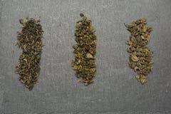Τρεις ποικιλίες του πράσινου τσαγιού επάνω; σκοτεινό υπόβαθρο στοκ εικόνες