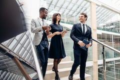 Τρεις πολυφυλετικοί επιχειρηματίες που περπατούν κάτω στα σκαλοπάτια με την ψηφιακή ταμπλέτα στοκ φωτογραφία με δικαίωμα ελεύθερης χρήσης