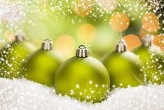 Τρεις πράσινες διακοσμήσεις Χριστουγέννων στο χιόνι πέρα από ένα αφηρημένο υπόβαθρο Στοκ φωτογραφία με δικαίωμα ελεύθερης χρήσης