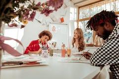 Τρεις σπουδαστές τέχνης που αισθάνονται πολυάσχολοι σύροντας στο διακοσμημένο στούντιο στοκ εικόνες