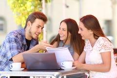 Τρεις σπουδαστές που μελετούν και που μαθαίνουν σε μια καφετερία