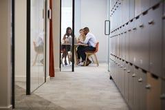 Τρεις συνάδελφοι που χρησιμοποιούν το φορητό προσωπικό υπολογιστή σε μια συνεδρίαση των γραφείων στοκ φωτογραφία με δικαίωμα ελεύθερης χρήσης