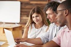 Τρεις συνάδελφοι εργάζονται μαζί στο φορητό προσωπικό υπολογιστή, κλείνουν επάνω στοκ φωτογραφία με δικαίωμα ελεύθερης χρήσης
