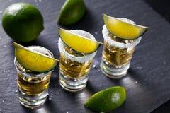 Τρεις σωροί του μεξικάνικου χρυσού tequila με τον ασβέστη και το άλας στοκ φωτογραφία