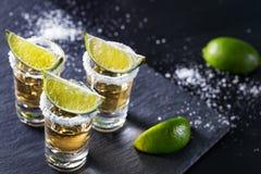 Τρεις σωροί του tequila με τον ασβέστη και το άλας στοκ φωτογραφία