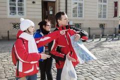 Τρεις τουρίστες εξετάζουν το χάρτη της έλξης πόλεων ` s Στοκ Εικόνες