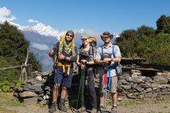 Τρεις τουρίστες backpackers που θέτουν, κορυφογραμμή αιχμών βουνών χιονιού Στοκ εικόνες με δικαίωμα ελεύθερης χρήσης