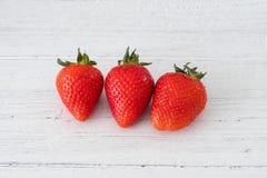 Τρεις υγιείς σκωτσέζικες φράουλες σε έναν λευκό πίνακα σανίδων στοκ φωτογραφίες με δικαίωμα ελεύθερης χρήσης