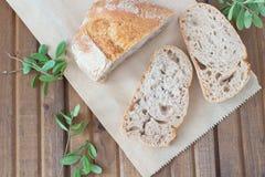 Τρεις φέτες του ψωμιού και των πράσινων φύλλων στον πίνακα Στοκ Φωτογραφία