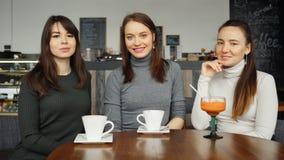 Τρεις φίλες γυναικών με τα ποτά σε έναν καφέ μιλούν στοκ φωτογραφίες