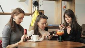 Τρεις φίλες γυναικών σε έναν καφέ κοιτάζουν βιαστικά τα κινητά τηλέφωνά τους Φιλική συνεδρίαση στον καφέ στοκ εικόνες με δικαίωμα ελεύθερης χρήσης