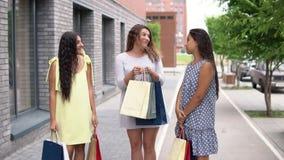 Τρεις φίλες κοριτσιών συζητούν τις αγορές μετά από να ψωνίσουν κίνηση αργή HD απόθεμα βίντεο