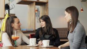 Τρεις φίλες σε έναν καφέ μιλούν και πίνουν τα ποτά τους στοκ φωτογραφία με δικαίωμα ελεύθερης χρήσης