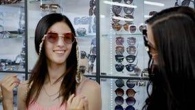 Τρεις φίλες χαίρονται τα επίκτητα γυαλιά ήλιων απόθεμα βίντεο