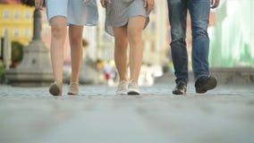 Τρεις φίλοι περπατούν στο πεζοδρόμιο στη μεσημβρία Έχουν τη διασκέδαση σε αυτόν τον ηλιόλουστο και καιρό θερμότητας φιλμ μικρού μήκους