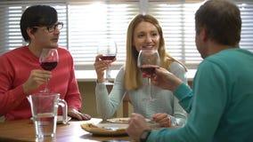 Τρεις φίλοι που πίνουν το κόκκινο κρασί στο εστιατόριο φιλμ μικρού μήκους
